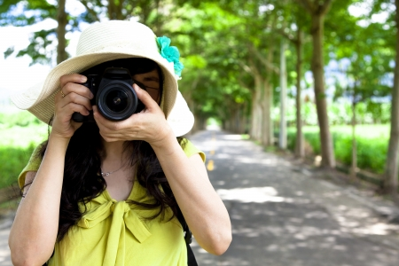 taking photograph: Young traveler taking photo in the green forest Stock Photo