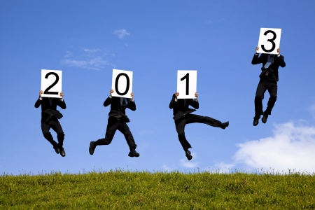 businessman holding 2013  and jumping on the green field photo