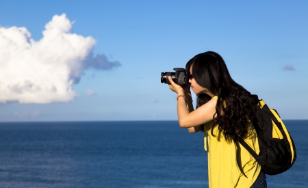 Young woman taking photo with cloud background photo