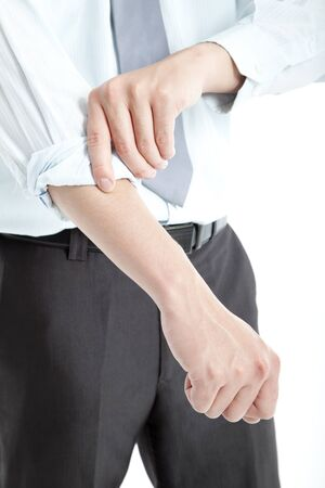 difficult task: Businessman rolling his sleeves up