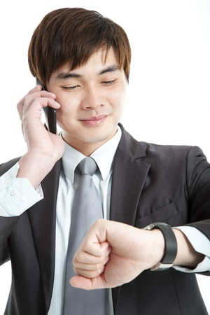 businessman waiting call: asian businessman checking time while talking on mobile phone
