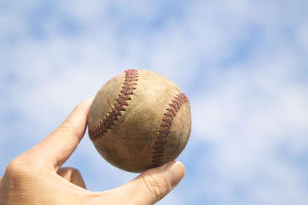 hand holding old baseball with cloud background photo