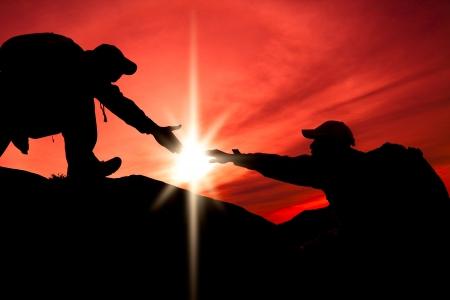 bergbeklimmen: Silhouet van helpende hand tussen twee klimmer