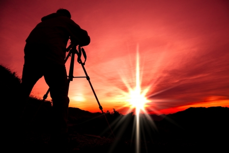 tripod: Silhouette of photographer on the top of mountain Stock Photo