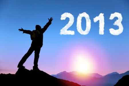 happy new year 2013. young man standing on the top of mountain watching the sunrise and cloud 2013 Stock Photo - 14622075