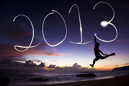 happy new year 2013. young man jumping and drawing 2013 by flashlight in the air on the beach before sunrise photo