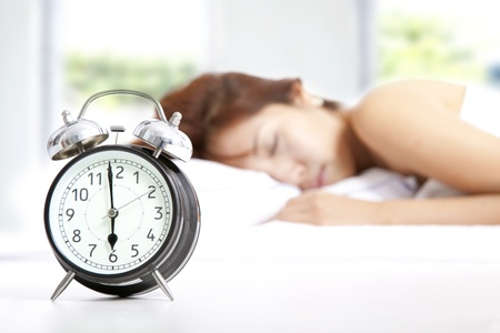 oversleep: The clock and Young beautiful woman sleeping Stock Photo