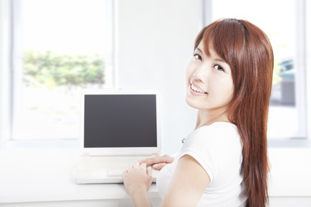 happy young asian woman browsing the internet using the laptop at home photo