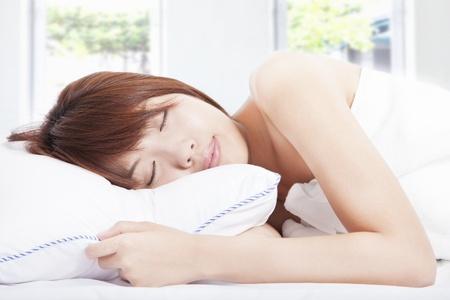 coussins: jeune femme dormant dans le lit