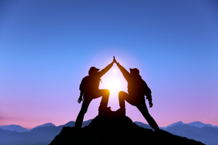 성공 제스처가 산의 정상에 서있는 두 사람의 실루엣 스톡 콘텐츠