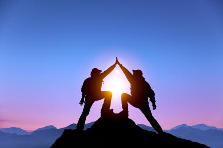 bergbeklimmen: Het silhouet van twee man met succes gebaar staande op de top van de berg Stockfoto