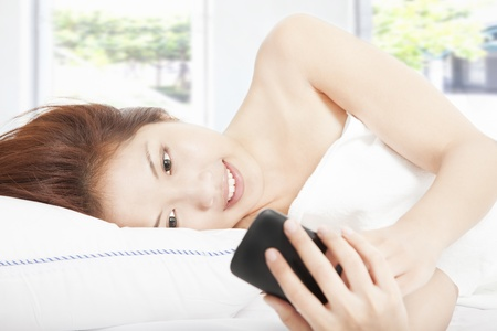 smiling young woman texting by smart phone on the bed  photo
