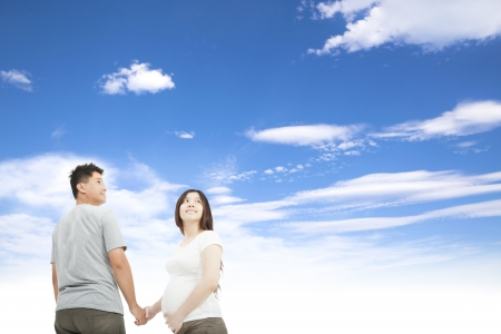 pregnant couple: husband holding pregnant wifes hand and cloud background Stock Photo