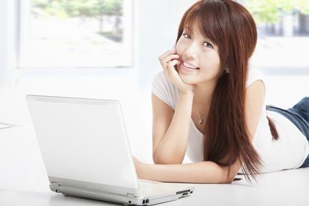 asian young woman lying on floor doing homework on laptop Stock Photo - 14742213