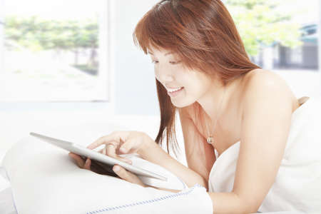 young woman using tablet on the bed photo