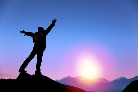 cima montagna: giovane uomo in piedi sulla cima della montagna e guardare il sorgere del sole