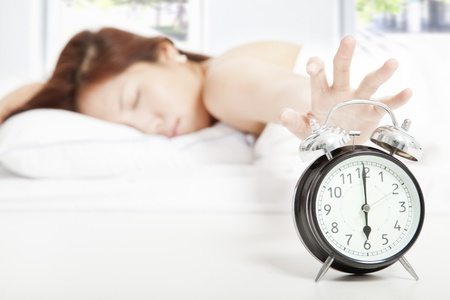 off: Woman turning off the alarm clock Stock Photo