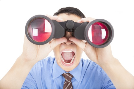 surprised businessman looks through binoculars and isolated photo