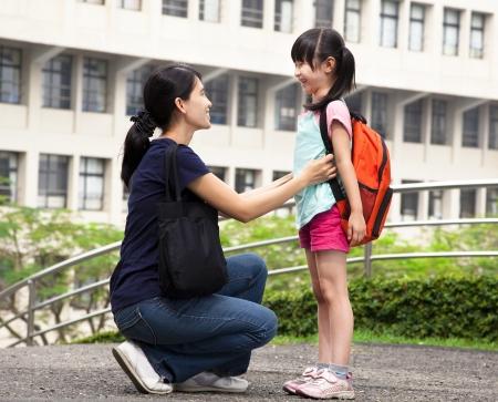 mochila escolar: volver a la escuela asiática madre feliz con su hija en la escuela