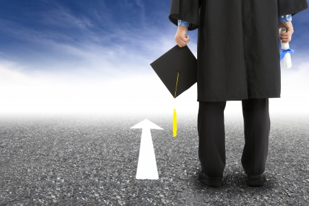 college graduate: graduate standing on the road and forward arrow Stock Photo