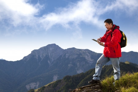 young man touching the  tablet pc on the top of mountain photo
