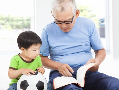 senior reading: grandfather reading a story book for his grandson