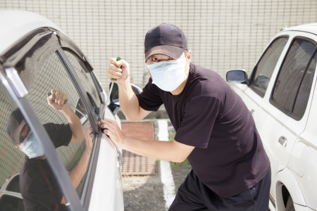 robo de autos: hombre en la máscara tratando de robar un coche Foto de archivo