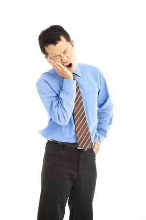 young businessman in agony with a toothache over white background photo