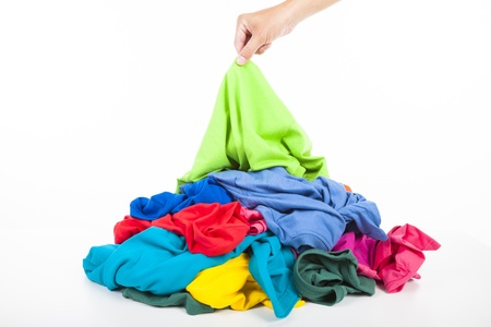 chose: hand pick up a shirt in pile of colorful clothes Stock Photo