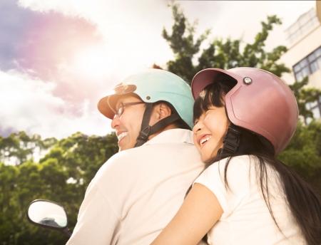 casco de moto: padre feliz con la hija en la bicicleta Foto de archivo