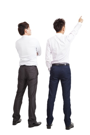 hands behind back: full length of two businessman pointing and looking