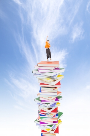 happy kid jumping on the books Stock Photo - 15333542
