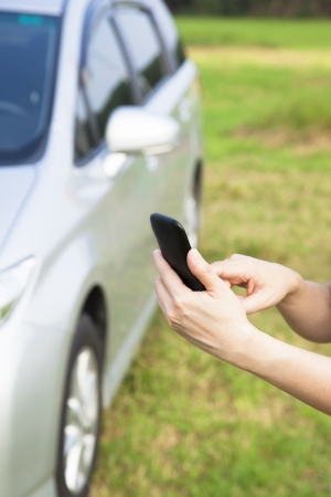 calling for help: hand touching the smart phone before a car and calling for help