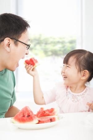 familia comiendo: niña feliz con las frutas que comen padre