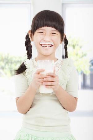 tomando leche: Ni�a feliz con un vaso de leche fresca