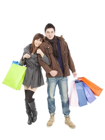 happy young asian couple with shopping bags isolated on white photo