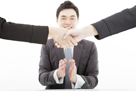 handshaking against businessman applauding hands photo