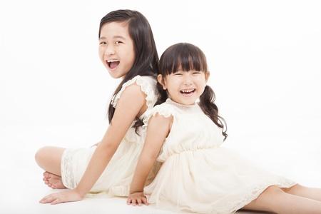 ni�os riendose: ni�as felices sentados en el fondo blanco Foto de archivo