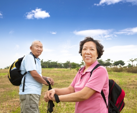 asian Senior couple hiking in countryside photo