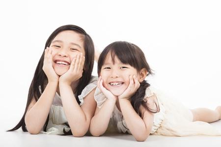 ni�os sentados: dos muchachas asi�ticas felices en el fondo blanco Foto de archivo