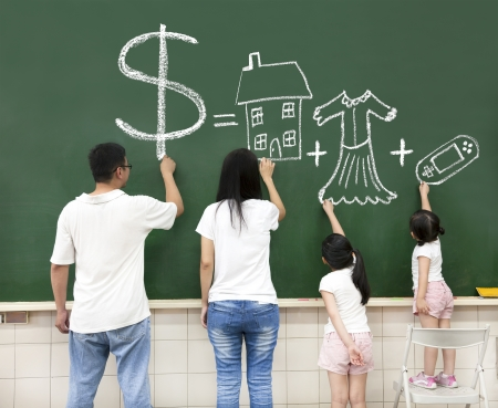 money in hand: family drawing money house clothes and video game symbol on the chalkboard Stock Photo