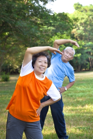 Happy asian senior fitness couple in the park photo
