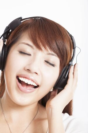 asian woman listening and enjoying music in headphones photo