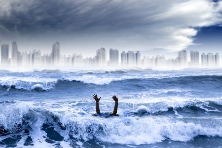 ahogandose: el calentamiento global y el concepto de clima extremo. hombre que se ahoga en el agua y la tormenta destruy� la ciudad Foto de archivo