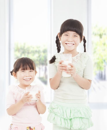 glass of milk: two little girls holding a glass of fresh milk  Stock Photo