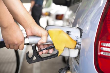 bomba de gasolina: mano volver a llenar el coche con el combustible en una estaci�n de llenado