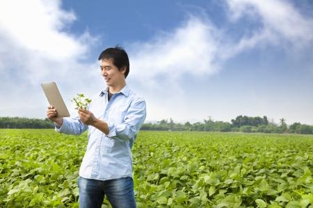 joven agricultor: granjero asi�tico con tablet pc Foto de archivo