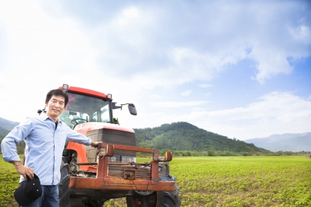 happy asian farmer with Old tractor on the grass field photo