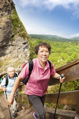 woman hiking: happy asian senior couple hiking in the mountain