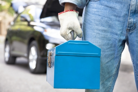 toolbox: car mechanic holding toolbox and standing before vehicle Stock Photo